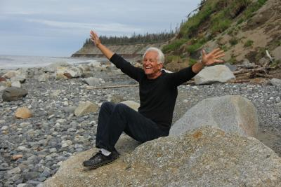 Healthy aging older man smiling with hands wide on the beach