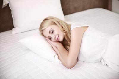 Woman sleeping peacefully in her bed while smiling