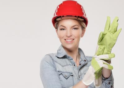 Woman with a hard hat on and cleaning gloves getting ready to work