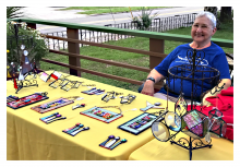 Barbara Wakefield, a Gainesville Fine Arts Association artist, sits behind her stained glass art.